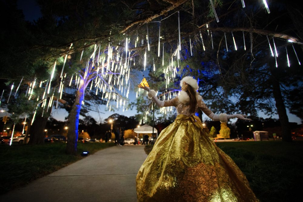 Finely dressed woman holidng a small gold pyramid and standing under a lighted tree.