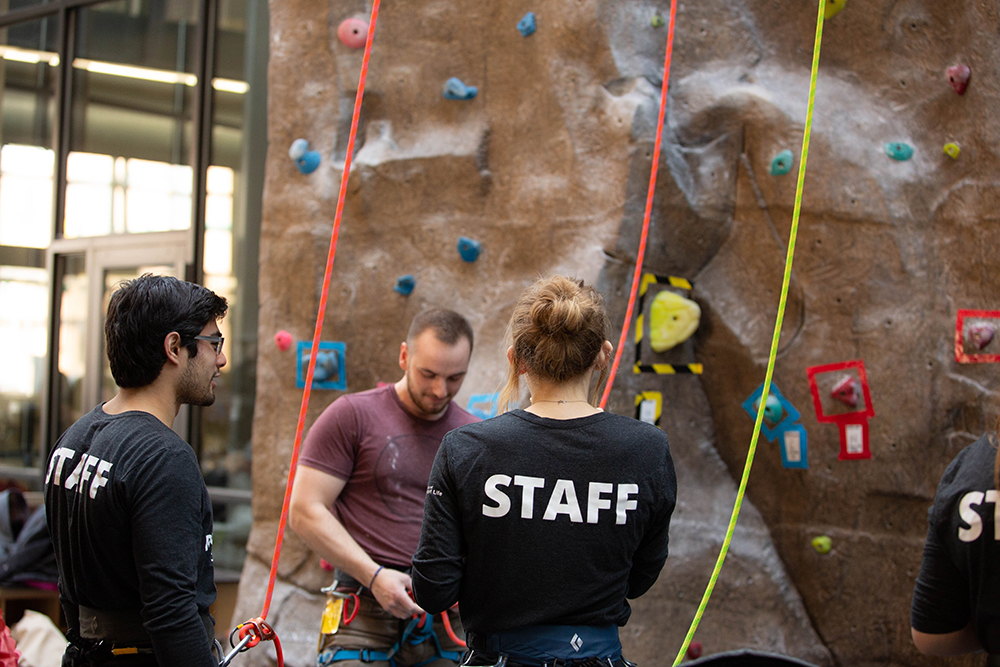 Two individuals with Staff written on their shirts helping another individual prepare to climb the climbing wall at the Campus Recreation and Wellness Center